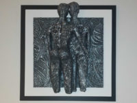 28cmx28cm lava and ceramic sculpture of man and woman embracing. Mounted on wood 28. Artist - Jesús Torrez